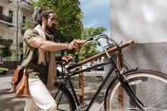 Allvarlig trevlig man som rymmer hans cykel Arkivfoto