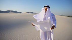 Allvarlig ung affärsman för arabUAE-shejk som betraktar konstruktionsplanet som står bland bred öken på varm sommardag lager videofilmer