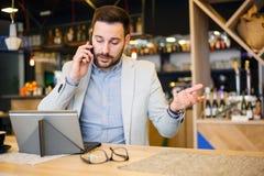 Allvarlig ung affärsman som talar på en telefon som arbetar i ett kafé arkivbild