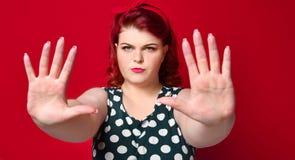 Allvarlig ung caucasian gest f?r kvinnavisningstopp med hennes hand royaltyfri foto