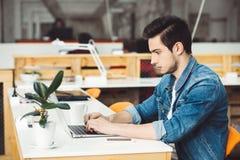 Allvarlig ung grabb med skägget som arbetar på bärbara datorn arkivbild