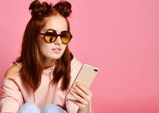 Allvarlig ung kvinna i den moderiktiga eyewearen som koncentreras på information som ser telefonen fotografering för bildbyråer