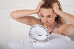 Allvarlig ung kvinna i säng som ser henne i en liten bärbar handspegel Arkivbild