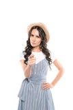 Allvarlig ung kvinna i sugrörhatt som pekar på kameran Arkivbild