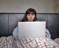 Allvarlig ung kvinna som sitter i säng under räkningarna med en bärbar dator arkivfoto