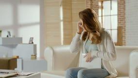 Allvarlig ung kvinna som talar på telefonen som kallar till supporttjänst lager videofilmer