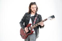 Allvarlig ung manlig gitarrist som står och spelar den elektriska gitarren arkivfoto