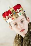 Allvarlig ung pojke i kunglig kappa och krona Royaltyfria Foton