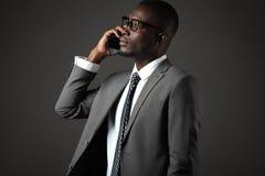 Allvarlig ung svart man med exponeringsglas och grått samtal för affärsdräkt royaltyfri fotografi