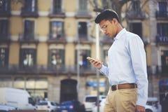 Allvarlig upptagen student i glasögon som skriver smsmeddelandet på smartphoneapplikation Arkivfoto