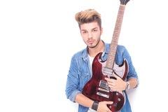 Allvarlig vippa som rymmer den röda elektriska gitarren Arkivbild