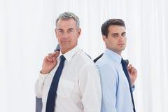 Allvarliga affärsmän som tillbaka poserar för att dra tillbaka tillsammans Arkivbild
