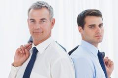 Allvarliga affärsmän som tillbaka poserar för att dra tillbaka tillsammans, medan rymma t Arkivbild