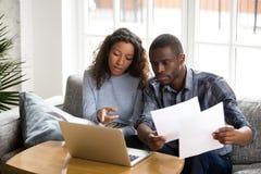 Allvarliga afrikansk amerikanpar som diskuterar pappers- dokument arkivfoto