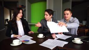 Allvarliga arbetare och affärsmän, två grabbar och flickan diskuterar om affär och ser dokument i mapp, sitter på tabellen arkivfilmer