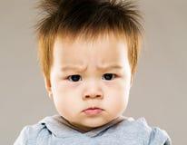 Allvarliga asia behandla som ett barn pojken som ögonbrynet rynkar pannan Arkivfoto
