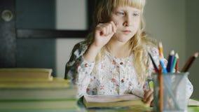 Allvarliga blonda flickaattraktioner på tabellen I förgrunden, en vas med kulöra blyertspennor och en bunt av böcker lager videofilmer