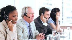 Allvarliga call centermedel som talar med hörlurar med mikrofon lager videofilmer