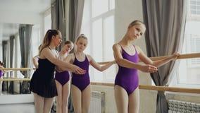 Allvarliga flickor är praktiserande armförehavanden under balettkurs i studio Hjälper den yrkesmässiga ballerina för läraren lager videofilmer