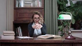 Allvarliga härliga bärande exponeringsglas för ung kvinna som stirrar på kameran och gnider hennes händer på hennes arbetsplats arkivfilmer
