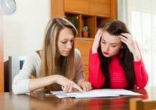 Allvarliga kvinnor som ser finansiella dokument på tabellen Royaltyfri Bild