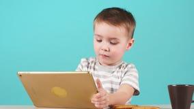 Allvarliga Little Boy anv?nder minnestavlan p? bl? bakgrund lager videofilmer
