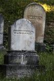 Allvarliga markörer för fader och för make på en gammal kyrkogård arkivbild