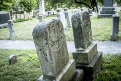 Allvarliga markörer för fader och för moder på en gammal kyrkogård arkivbild