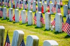 Allvarliga markörer med amerikanska flaggan i en militär kyrkogård Royaltyfria Bilder