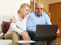 Allvarliga mogna par som ser dokument i bärbar dator Royaltyfri Foto