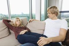 Allvarliga par som hemma ser de på soffan Fotografering för Bildbyråer