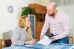 Allvarliga par som läser finansiella dokument Arkivbilder