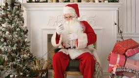 Allvarliga Santa Claus som kontrollerar hans julpost på telefonen Arkivbilder