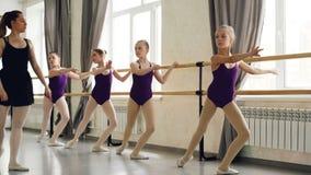 Allvarliga små flickor lär följd av balettpositioner på balettgrupp med den hjälpsamma läraren Rymligt ljus lager videofilmer