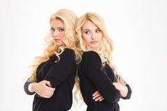 Allvarliga systrar kopplar samman med vikta armar Fotografering för Bildbyråer