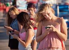 Allvarliga tonåringar på Smartphones Fotografering för Bildbyråer