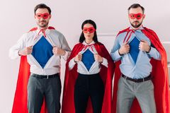 allvarliga toppna businesspeople i maskeringar och uddar som visar blåa skjortor royaltyfri fotografi