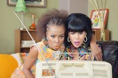 Allvarliga vänner som håller ögonen på TV Royaltyfria Foton