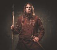 Allvarliga viking med ett spjut i traditionell kläder för en krigare som poserar på en mörk bakgrund Royaltyfri Bild