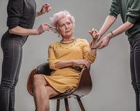 Allvarligt äldre kvinnligt sammanträde på stol i studio fotografering för bildbyråer