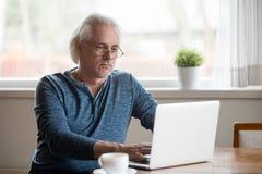 Allvarligt åldrigt manligt upptaget arbete på bärbara datorn hemma arkivbild