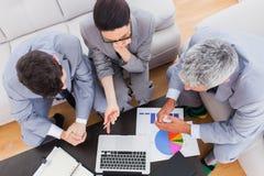 Allvarligt affärsfolk som tillsammans använder bärbara datorn och arbete på sof Arkivfoto