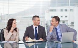 Allvarligt affärsfolk som tillsammans talar, medan vänta på som är inter- Arkivbild