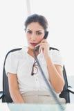 Allvarligt affärskvinnasammanträde på hennes skrivbord på telefonen Arkivfoto