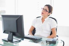 Allvarligt affärskvinnasammanträde på hennes skrivbord som ser datoren Arkivbilder
