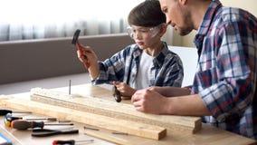Allvarligt bulta för fader och för son spikar i träplankan, familjfritid, service royaltyfria bilder