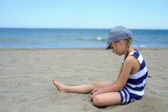 Allvarligt gulligt liten flickasammanträde på stranden Arkivfoton