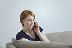 Allvarligt kvinnligt meddela på mobiltelefonen Arkivbild