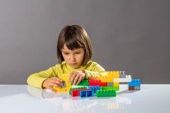 Allvarligt litet barn som spelar med byggnadstegelstenar med teknikerfantasi royaltyfria bilder