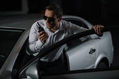 allvarligt manligt hemligt medel i solglasögon genom att använda talkiewalkie fotografering för bildbyråer